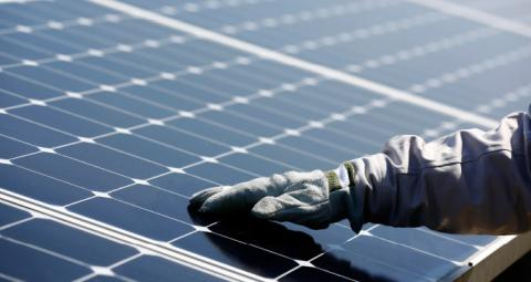 A gloved hand on a solar panel of the photovoltaic power plant started up by ISE, Total and SunPower in Nanao, Japan.