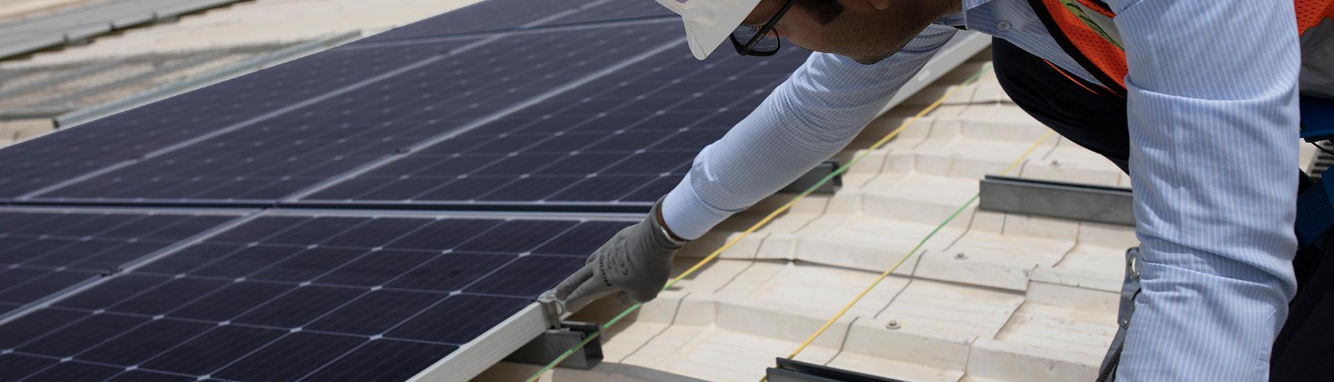 Employee installing Solar panels on the rooftop at Emirates Glass LLC.